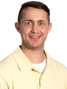 Elias, our Project Services Manager, is facing the camera at an angle, wearing a smile and a yellow ArcSource polo shirt.