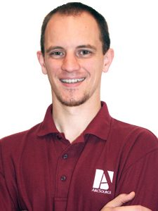 Eric, our Senior Tech Consultant, is smiling with arms folded across his chest and wearing a maroon ArcSource polo shirt.